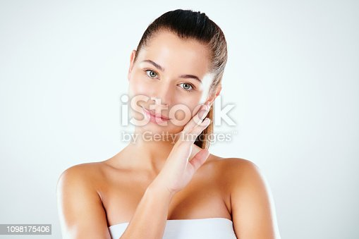 Studio shot of a beautiful young woman feeling her skin against a light background