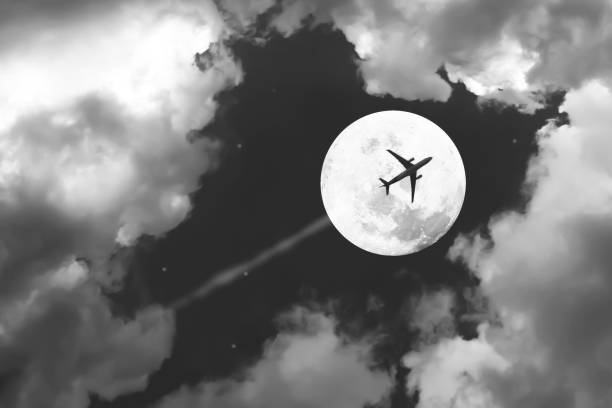 Beautiful dramatic atmosphere of airplane in black and white night sky with jet and full moon night. stock photo