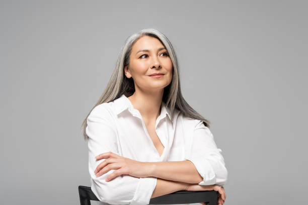 beautiful dreamy asian woman with grey hair sitting on chair isolated on grey stock photo