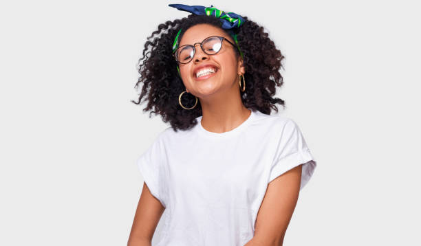 Beautiful dreamy dark-skinned young woman dressed in white t-shirt, feeling happy and enjoying the weather. African American female smiling broadly, wearing round eyewear posing over white studio wall stock photo