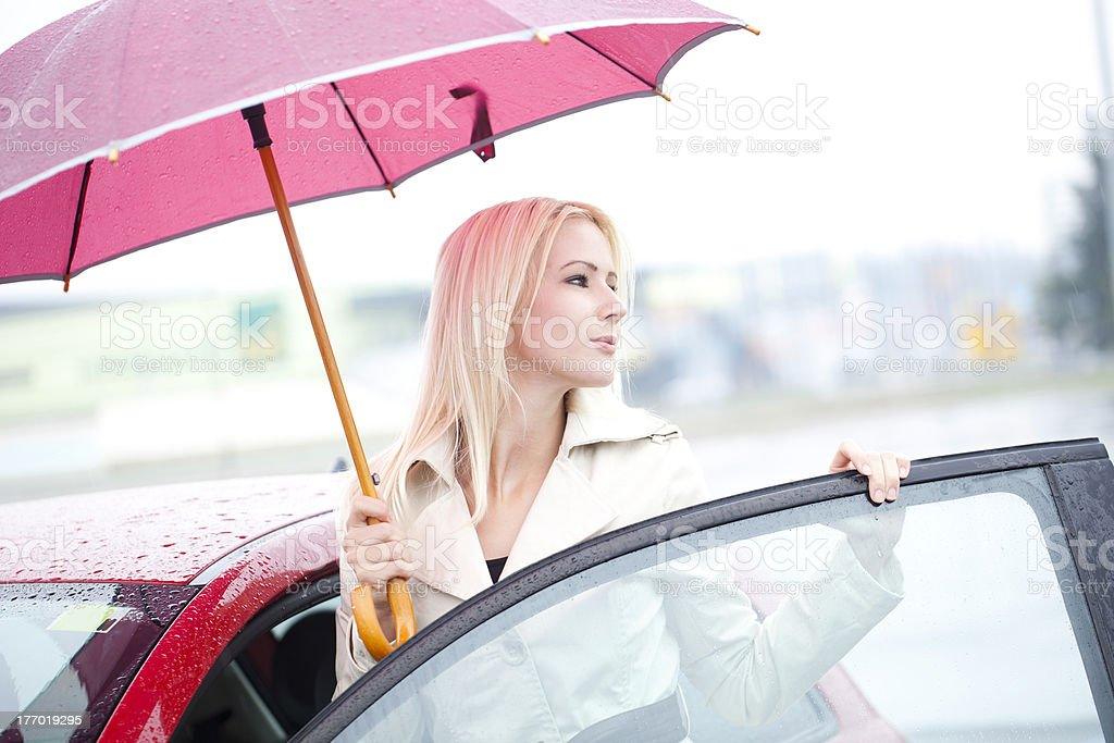 Beautiful Driver Just Out Of Car In A Rainy Day stock photo