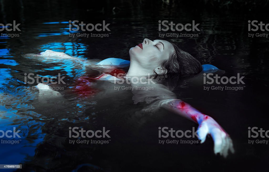 Beautiful drowned woman in bloody dress stock photo