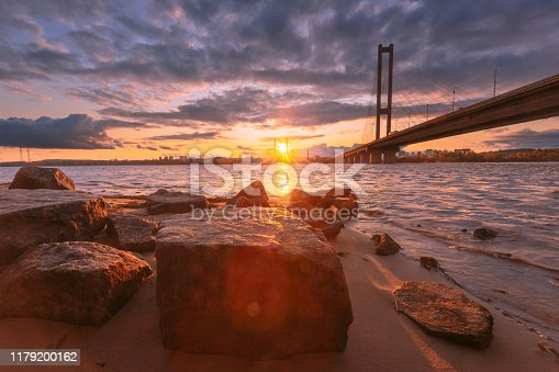 1130689824 istock photo Beautiful dusk landscape with bridge over river and textured stones on the sand on foreground. Dnipro river. Kyiv, Ukraine. Lens flare effect from sunlight. 1179200162