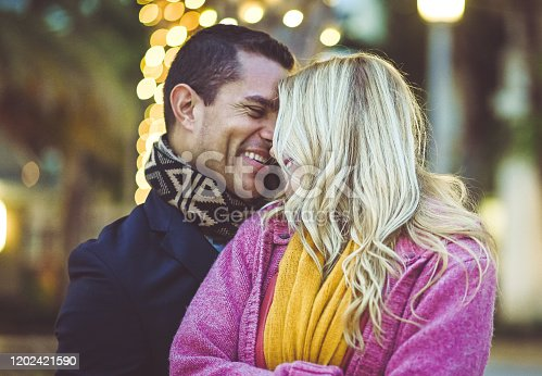 Beautiful couple, blonde woman and Latino man, are affectionate and snuggled up to each other while outdoors in an urban environment with twinkling lights behind them. They are dressed for cold weather and are happily hugging and candidly enjoying each other's company