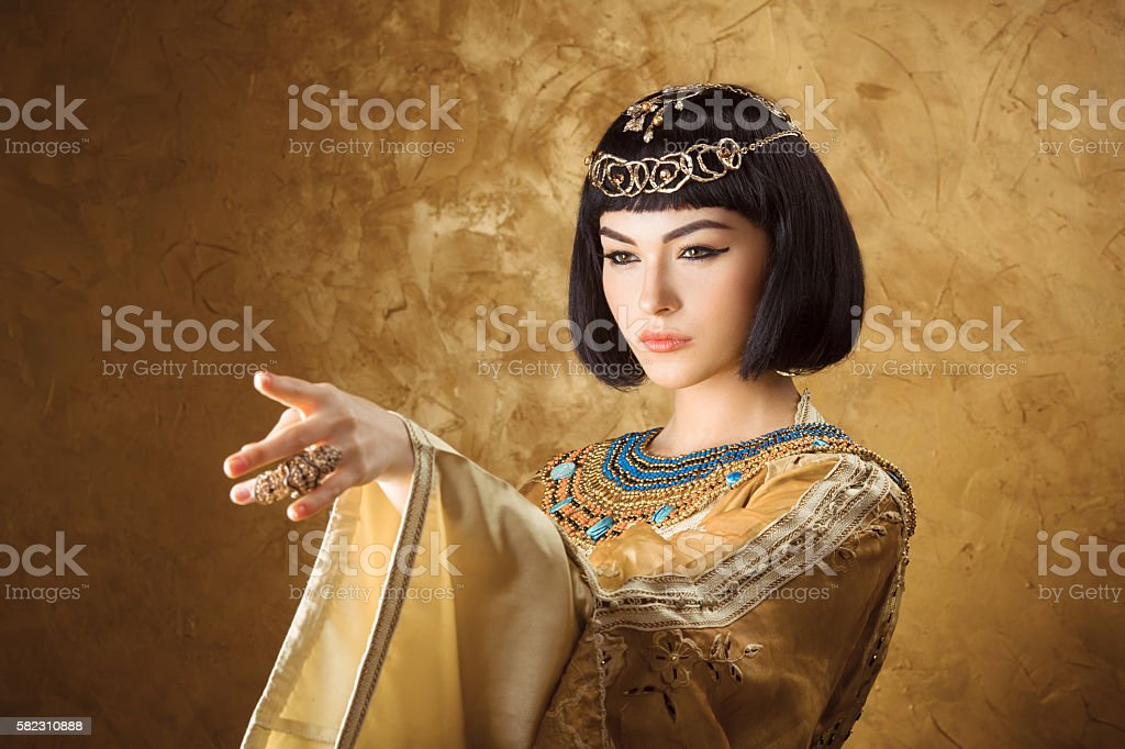 Beautiful Egyptian woman like Cleopatra pointing finger away on golden stock photo