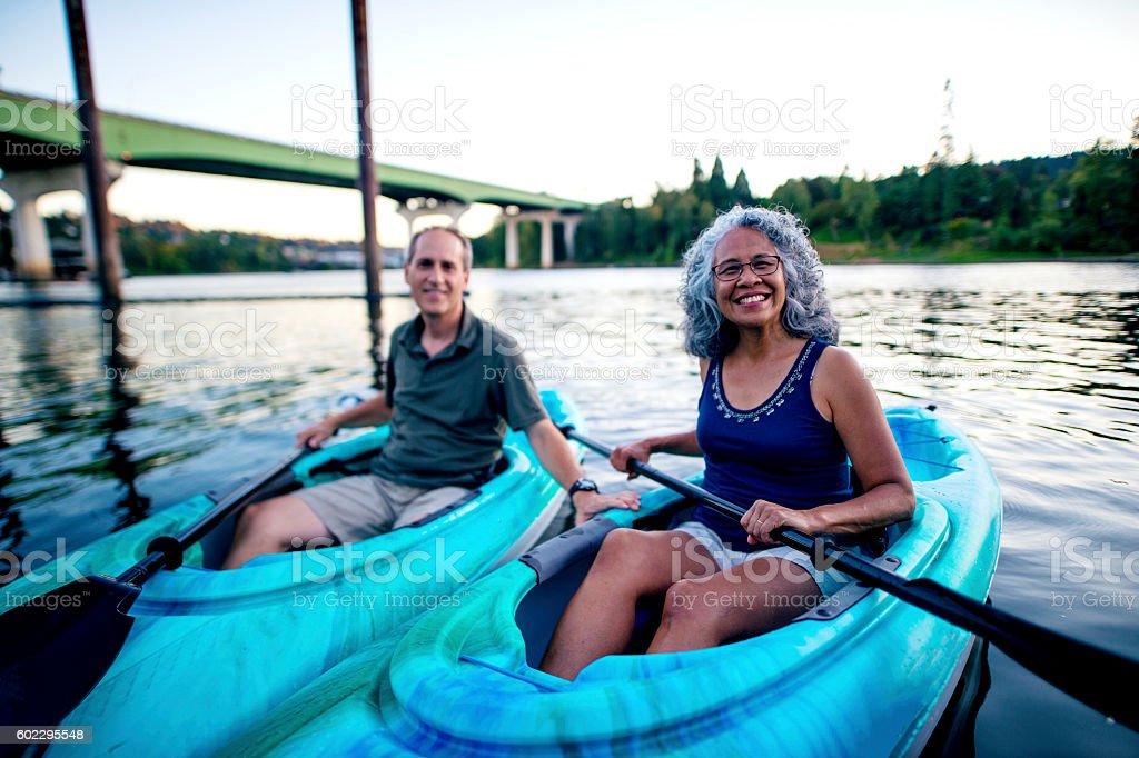 Beautiful elderly heterosexual couple kayaking stock photo