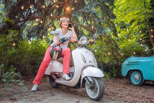schöne ältere seniorin auf retro-motorrad oder moped sprechen am telefon - sexy granny stock-fotos und bilder