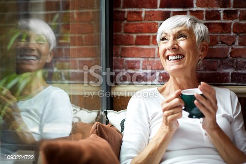 Beautiful elderly woman fondly recollecting while drinking a hot drink from a cup.