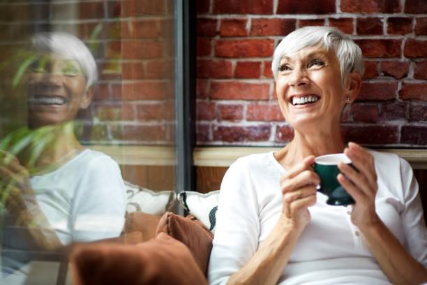 hermosa anciana con un nostálgico momento al tomar una bebida caliente de una taza - café bebida fotografías e imágenes de stock