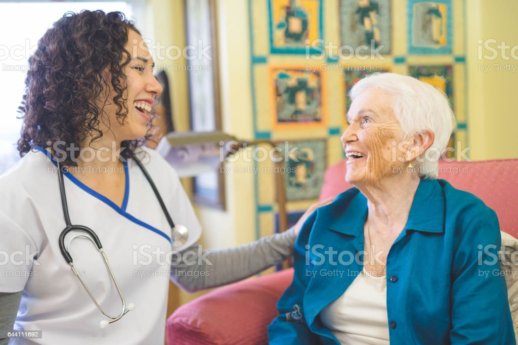 Beautiful elderly woman in apartment interacting with young Hawaiian nurse stock photo