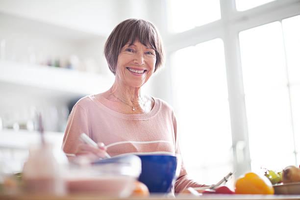 schöne ältere frau in der küche lächelnd - seniorenwohnungen stock-fotos und bilder