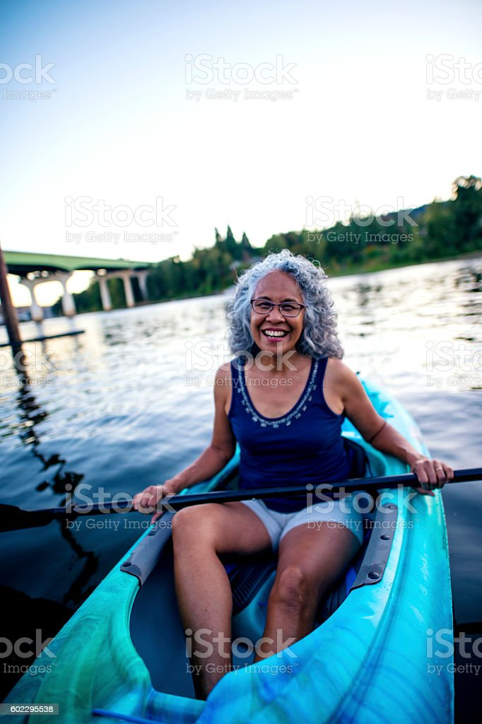 Beautiful elderly woman kayaking on the river stock photo
