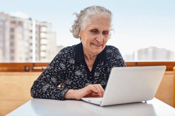 Beautiful elderly woman with white hair using a laptop computer on desk, urban skyline at the background. stock photo