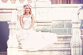 Beautiful bride sitting on steps of old and antique house