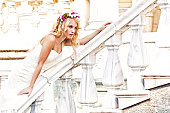 Beautiful bride leaning on balustrade of old and antique house