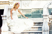 Beautiful bride sitting on of old and antique house
