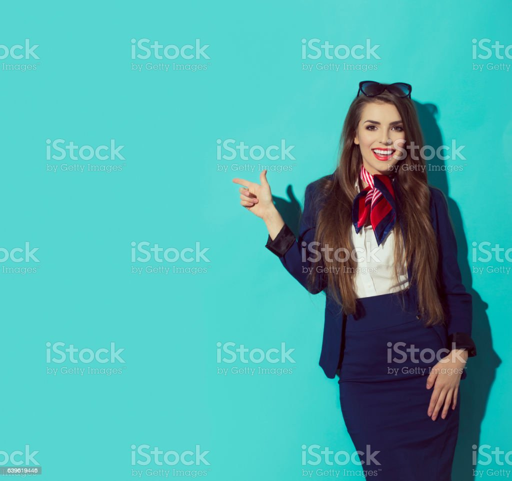 Beautiful elegant brunette female pointing to the left. Space stock photo