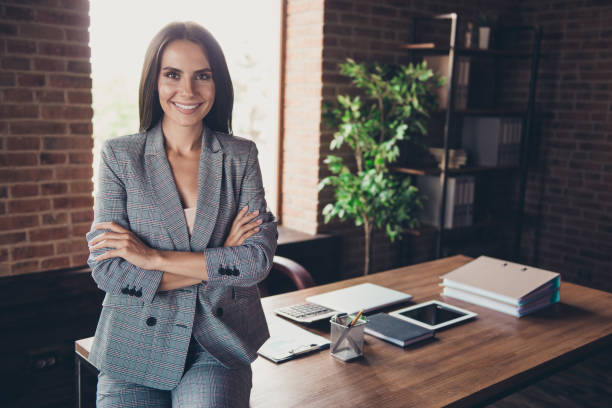 Beautiful elegant classic trendy latin smiling lady freelancer, company founder with folded crossed hands, wearing gray suit, invites to her team, at work place, station, modern fashionable loft stock photo