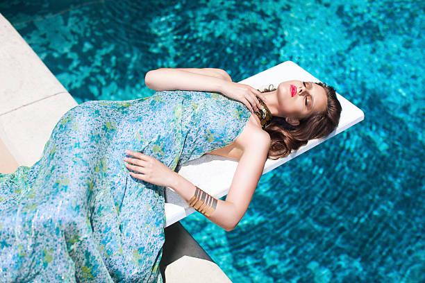 Beautiful Elegant Model Wearing Pretty Dress Laying By Pool stock photo