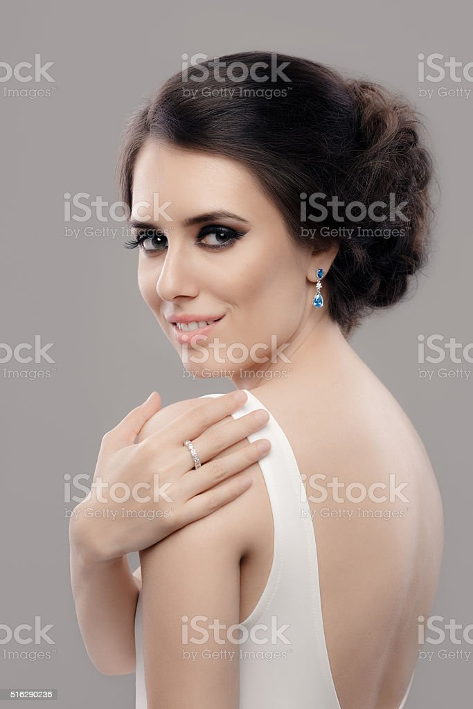 Beautiful Elegant Woman in White Dress Wearing Jewelry stock photo