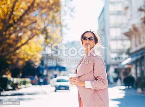 A young woman drinking coffee on her way to work.
