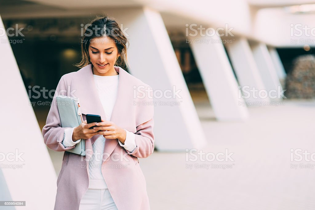 Beautiful elegant woman texting on the phone stock photo