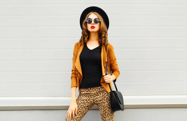 Hermosa mujer elegante con un sombrero elegante retro, gafas de sol, chaqueta marrón y bolso negro sobre fondo gris - foto de stock