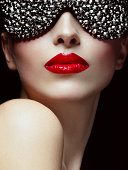 Studio beauty portrait of sensual woman with red lips and bizarre eyewear. Professional make-up. High-end retouch.