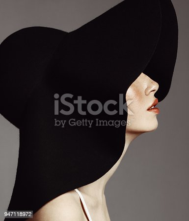 Studio portrait of elegant woman wearing big black hat.