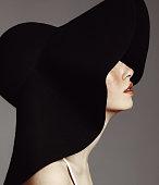 Studio portrait of elegant woman wearing big black hat.
