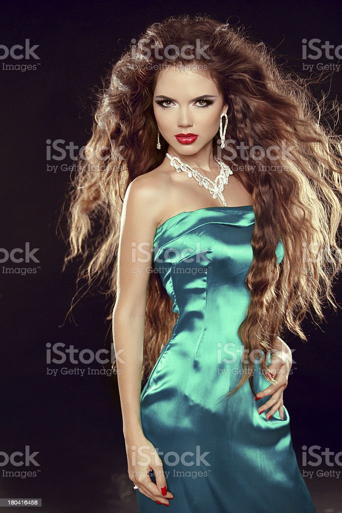 Beautiful elegant woman with long curly hairs in blue dress royalty-free stock photo