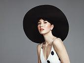 Studio portrait of elegant woman wearing big black hat