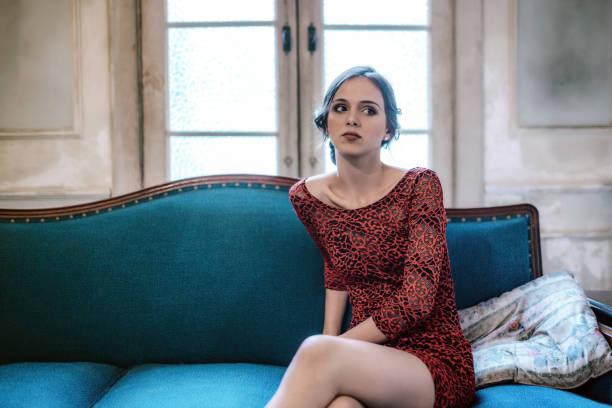 schöne elegante junge kubanische frau sitzt nachdenklich auf sofa - rot bekümmerte möbel stock-fotos und bilder