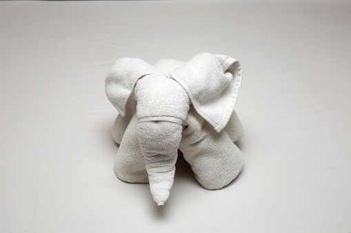 1131900491 istock photo Beautiful elephant figure rolled from hotel towels on the bed, Hotel Towels on Bed clean and new 1227219258