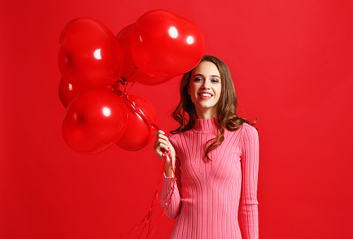 beautiful emotional girl in  pink dress with red ballons on red background