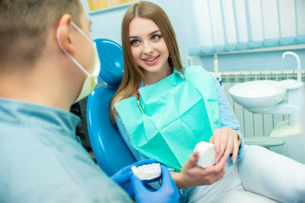 Beautiful emotional girl sitting in a dental chair next to a male doctor. Dental clinic Beautiful emotional girl sitting in a dental chair next to a male doctor. Dental clinic. Doctor and patient tranquilizing stock pictures, royalty-free photos & images