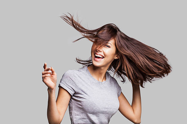 Beautiful emotional woman enjoying life Cute young girl with arms raised dancing and laughing and having fun long hair stock pictures, royalty-free photos & images