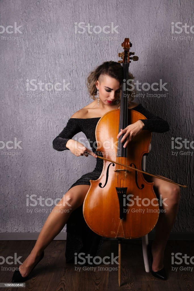 Beautiful Emotional woman in an evening dress playing the cello stock photo