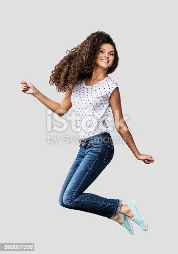 638678178 istock photo Beautiful emotional woman is jumping and having fun 883051938