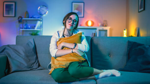 Beautiful Emotional Young Girl in Glasses Sitting on a Couch and Watching TV at Home. She is Hugging a Pillow. Screen Adds Reflections to Her Face. Cozy Room is Lit with Warm Light. Beautiful Emotional Young Girl in Glasses Sitting on a Couch and Watching TV at Home. She is Hugging a Pillow. Screen Adds Reflections to Her Face. Cozy Room is Lit with Warm Light. sentimentality stock pictures, royalty-free photos & images