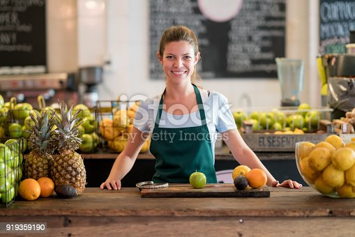 istock Beautiful employee of a juice bar standing behind the counter with apples, limes, oranges, pineapples on the table looking at camera smiling 919359190