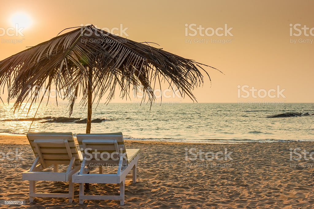 beautiful empty beach and a pair of sun loungers stock photo