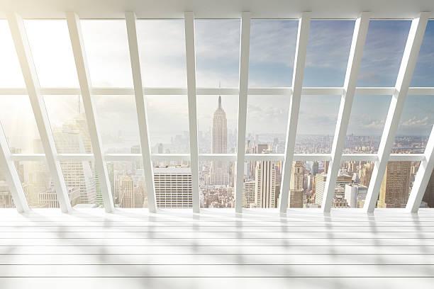 beautiful empty white loft interior with city view at dawn - fönsterrad bildbanksfoton och bilder