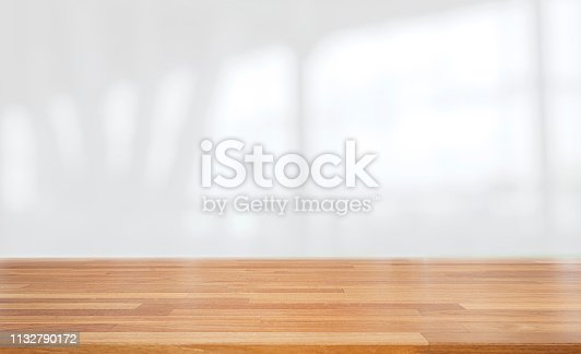 662984808 istock photo Beautiful empty wood table against abstract blur white interior background 1132790172