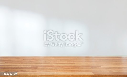 Beautiful empty wood table against abstract blur white interior background, montage, product display, indoor and windows