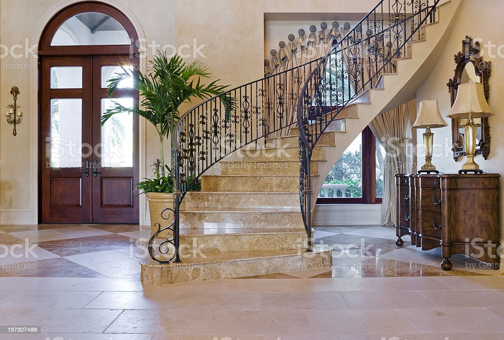 Beautiful Entryway with Custom Wrought Iron Staircase in Estate Home stock photo