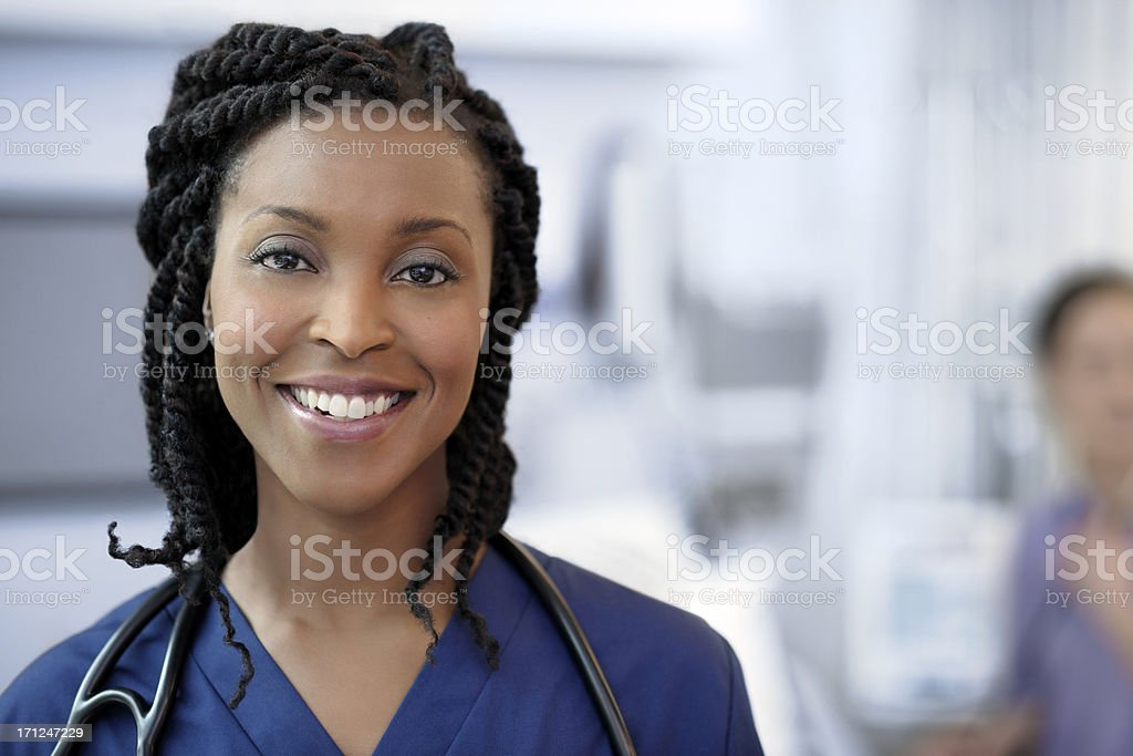 Beautiful ethnic female doctor examining a patient. stock photo