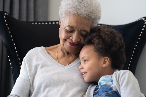 A young and attractive grandmother of African descent is spending time with her granddaughter. They are laughing.