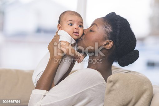 A beautiful young African American mother gently holds her infant daughter up in the air with both hands and kisses her cheek. The baby's eyes are wide open and she looks happy. They are sitting on a couch in their living room.