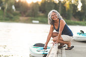 A beautiful older Hawaiian woman prepares to go river kayaking on a summer evening. She is lowering the kayak into the water and looking off-camera and smiling.